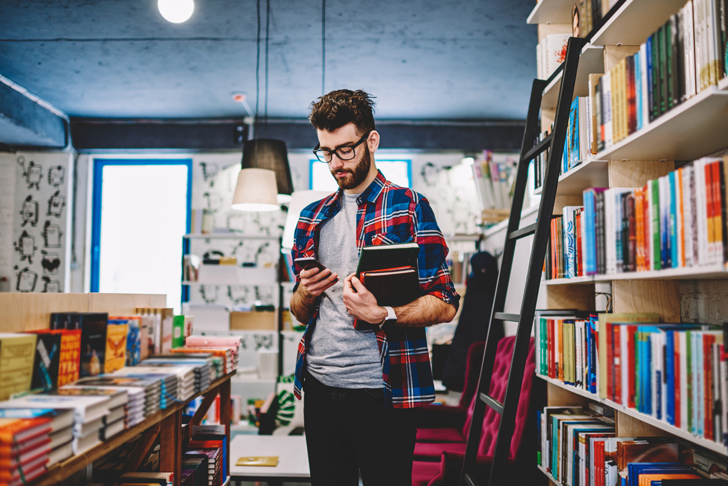Man on phone holding book in book store
